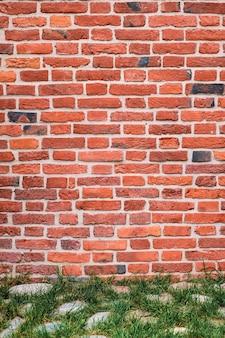 Rote backsteinmauer, altes hauswandmauerwerk. rahmen für hintergrund oder tapete. grünes gras und kopfsteinpflaster der straße an der wand