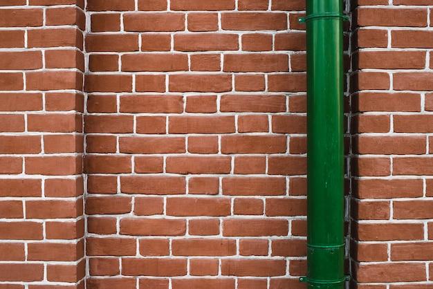 Rote backsteinmauer mit grünem fallrohr.