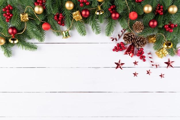 Rote bälle der weihnachtsgeschenkbox mit fichtenzweigen, kiefernkegel, rote beeren auf hölzernem backg