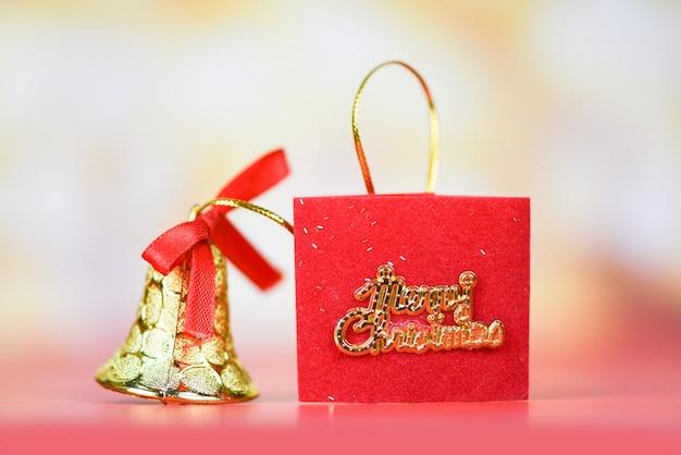 Rote bandglocke der weihnachtsdekoration mit hellem goldzusammenfassungsfeiertag