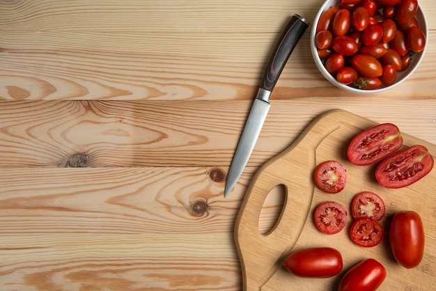 Rote beeren und geschnittene tomaten auf dem holztisch