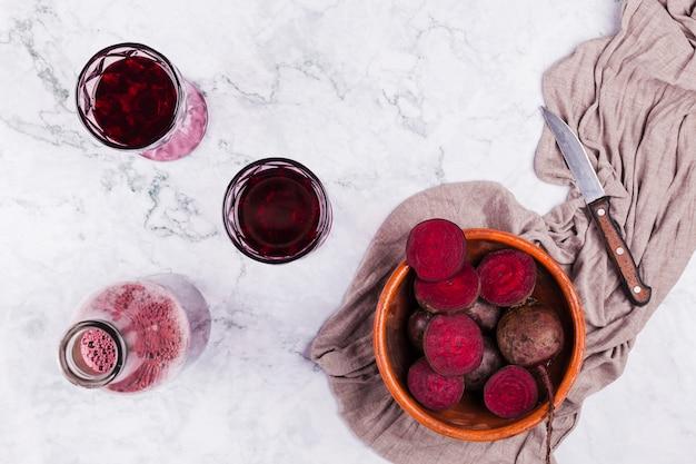 Rote beete mit einem glas saft schneiden