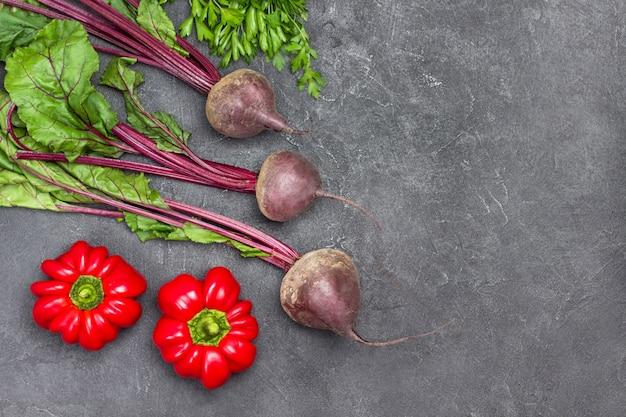 Rote beete mit grün und zwei paprika auf dem tisch. platz kopieren. flach liegen. schwarzer hintergrund