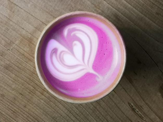 Rote beete super latte in einweg-pappbecher, draufsicht auf holz