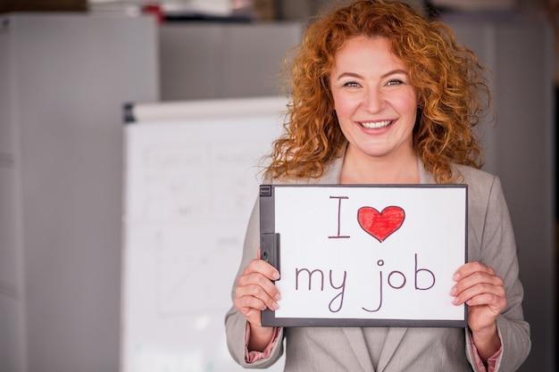 Rote behaarte lächelnde geschäftsfrau, die kleines plakat hält.