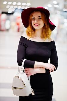 Rote behaarte mädchenabnutzung der mode auf schwarzem kleid und rotem hut mit dem damenrucksack warf im geschäftseinkaufszentrum auf.