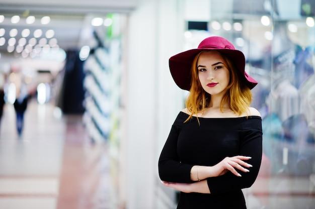 Rote behaarte mädchenabnutzung der mode auf schwarzem kleid und rotem hut warf im geschäftseinkaufszentrum auf.