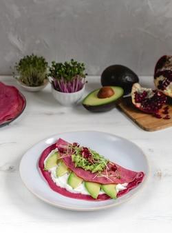 Rote-bete-pfannkuchen serviert auf teller mit avocado
