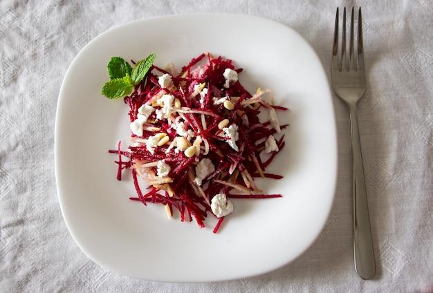 Rote-bete-salat mit feta, birnen und nüssen, die sonnenblumenöl anrichten.