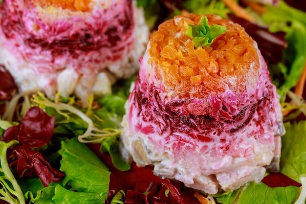 Rote-bete-salat mit hering und gemüse mit mayonnaise überzogen