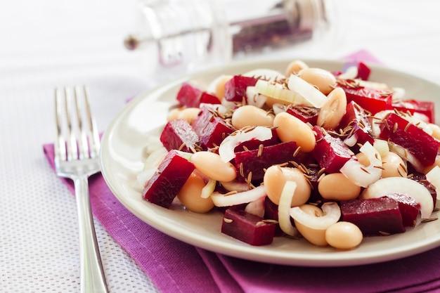 Rote-bete-salat mit weißen kidneybohnen gurken und zwiebeln mit öl angemacht mit kümmel