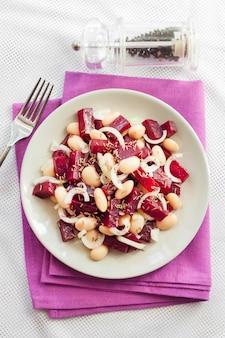 Rote-bete-salat mit weißen kidneybohnen gurken und zwiebeln mit öl angemacht