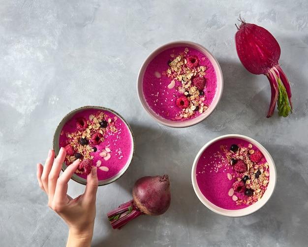 Rote-bete-smoothies mit haferflocken- und himbeerbeeren in einem teller auf einer grauen betonwand. die hand des mädchens legt himbeeren in einen teller. das konzept einer gesunden ernährung. draufsicht