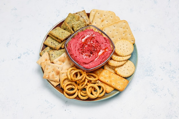 Rote-bete-wurzeln hummus auf schneidebrett mit salzigen plätzchen auf heller oberfläche
