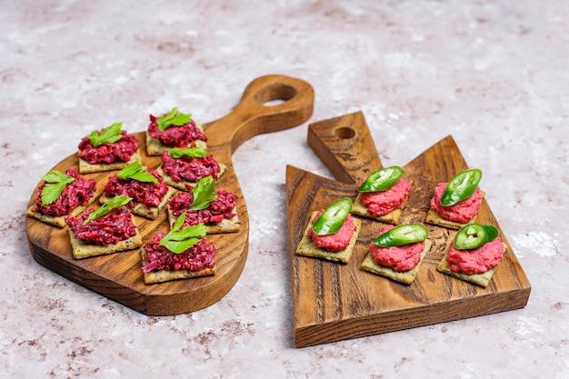 Rote-bete-wurzeln hummus canapes mit scheiben und petersilie des grünen pfeffers auf schneidebrett auf heller oberfläche