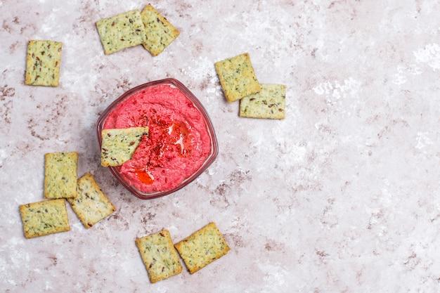 Rote-bete-wurzeln hummus mit salzigen plätzchen auf heller oberfläche