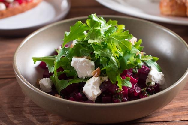 Rote-bete-wurzeln salat mit blauschimmelkäse, arugula und walnuss in einer platte