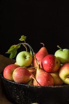 Rote birnen und äpfel holztisch, vegan, diätkost. herbsternte saftige früchte auf der tasche.