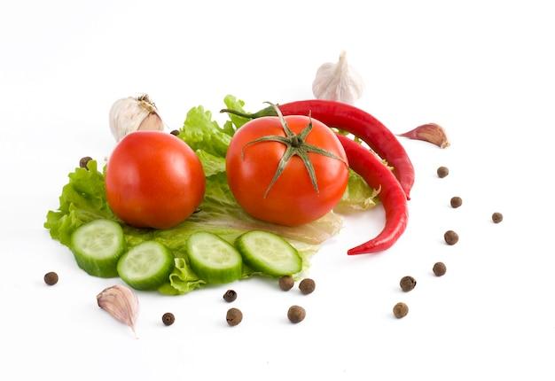 Rote bittere pfeffergurke und tomate auf einem weißen hintergrund. frisches gemüse auf einem abel hintergrund.