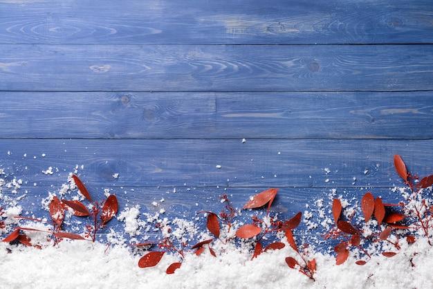 Rote blätter und schnee auf holztisch