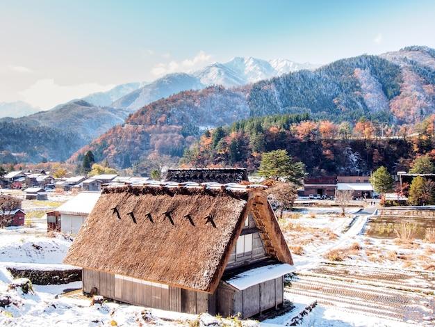 Rote blätter und schnee im herbst in shirakawa-go village, japan