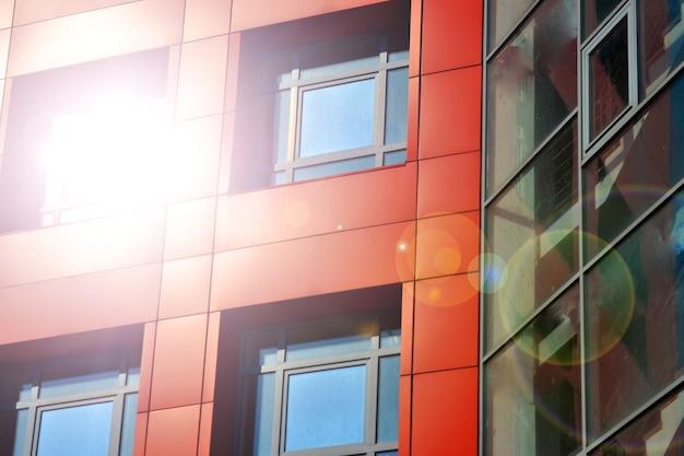Rote, blaue farbwände eines modernen gebäudes. teil der fassade des gebäudes im stil von high-tech-winkel. sonnenblendung