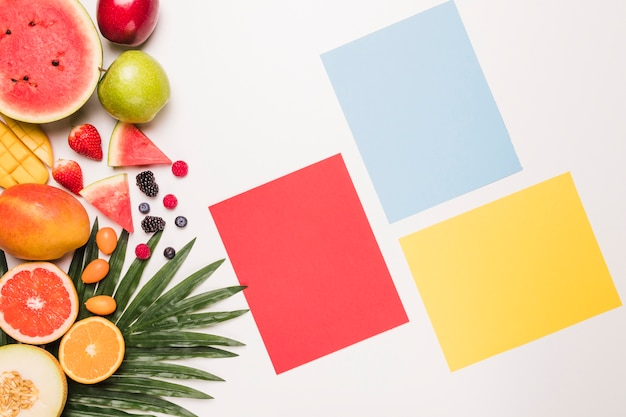 Rote blaue gelbe klebrige anmerkung und verschiedene früchte am palmblatt