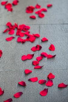 Rote blütenblätter auf dem boden auf dem bürgersteig