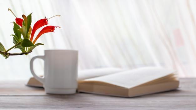 Rote blumen der zimmerpflanze nahe offenem buch und tasse kaffee