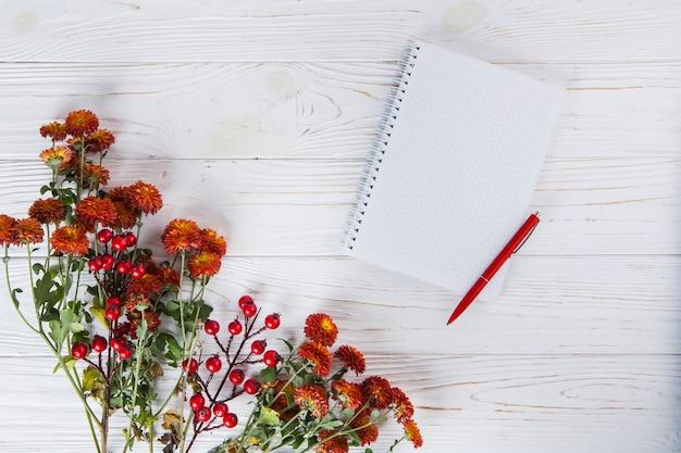 Rote blumen mit leerem notizbuch und stift auf holztisch