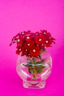 Rote blumen und vase in herzform - grußkarte zum valentinstag. studiofoto.