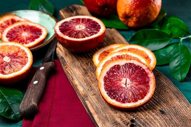 Rote blutige orange in scheiben geschnitten auf einem hölzernen schneidebrett nah oben