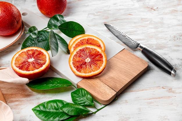 Rote blutige orange in scheiben geschnitten auf einem weißen schneidebrett nahaufnahme