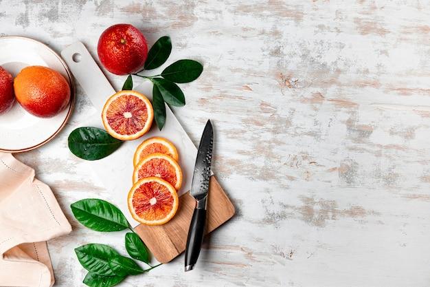 Rote blutige orangen schneiden in scheiben auf einem weißen schneidebrett draufsicht-copyspace