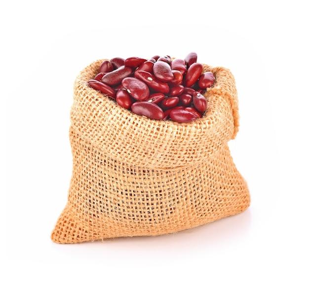 Rote bohnen in einer tasche auf weißem hintergrund