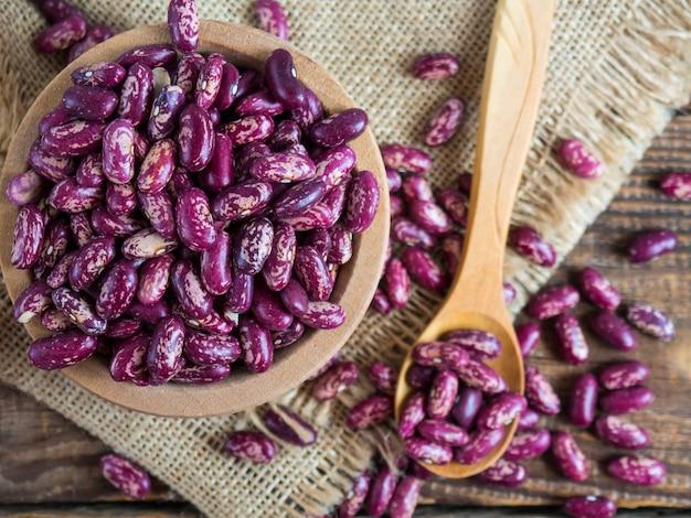 Rote bohnen mit einem muster. (köstliche bunte, rohe bohnen) in einer holzschale auf einem alten holztisch, hülsenfrüchte. platz kopieren