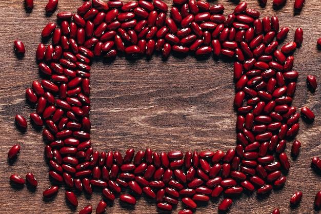 Rote bohnen schön auf einem hölzernen hintergrund ausgelegt. draufsicht. rechteckiger kopierraum. vegetarisches essen. unvorbereitet.