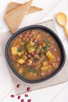 Rote bohnensuppe mit fleisch und kartoffeln in einer schwarzen tonschale