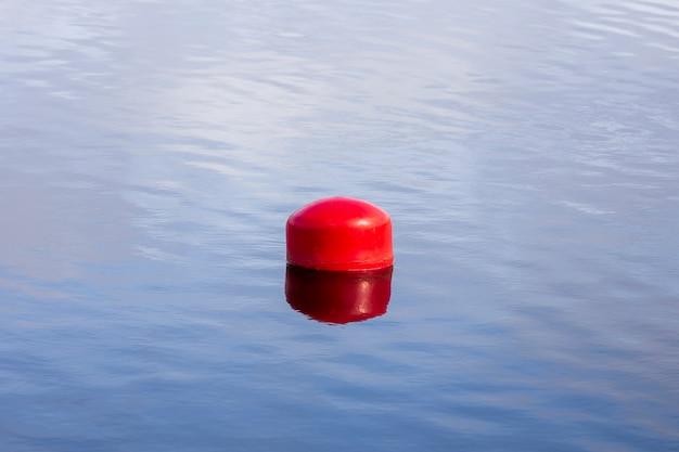 Rote boje auf dem wasser. zaun auf dem wasser. foto in hoher qualität