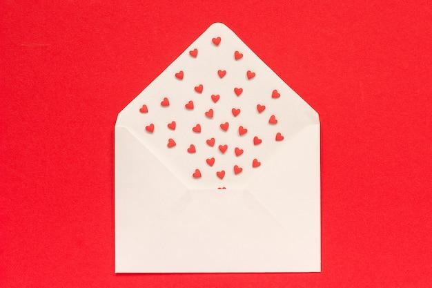 Rote bonbons besprüht süßigkeitsherzen aus weißem papierumschlag auf rotem hintergrund.