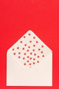 Rote bonbons besprüht süßigkeitsherzen, die aus weißbuchumschlag auf rotem hintergrund heraus fliegen.