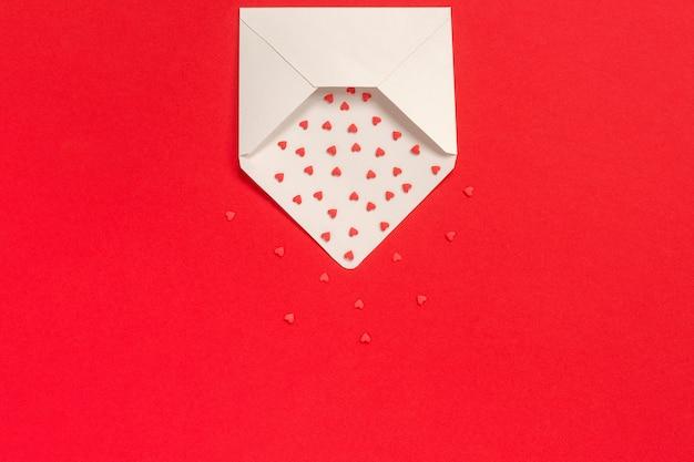 Rote bonbons besprüht süßigkeitsherzen fliegen aus weißbuchumschlag auf rotem hintergrund heraus.