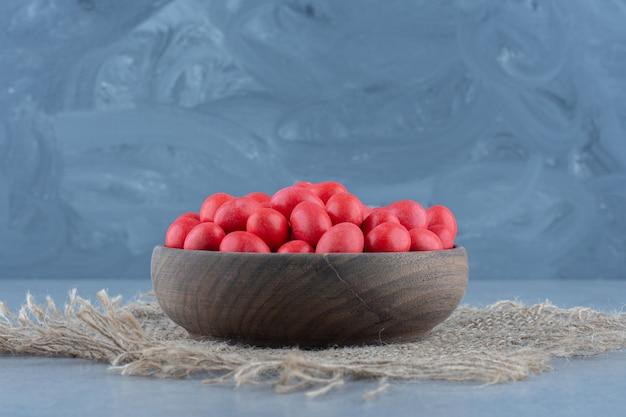 Rote bonbons in der tasse auf dem untersetzer, auf dem marmortisch.