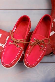 Rote bootsschuhe auf hölzernem hintergrund nahe rettungsring. draufsicht. nahansicht.