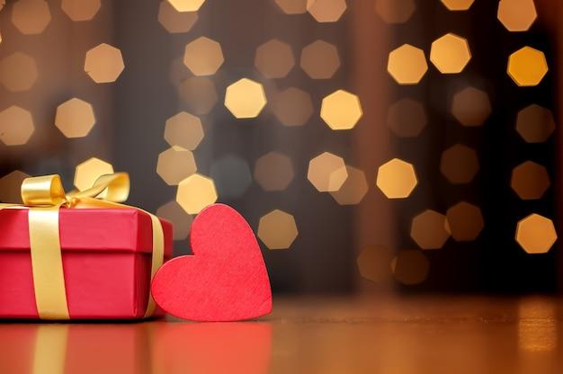 Rote box des roten herzens und des geschenks auf bokeh hintergrund.