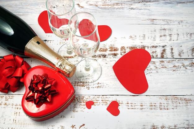 Rote box mit herzform mit schleife, flasche champagner und zwei gläsern, valentinstagsparty