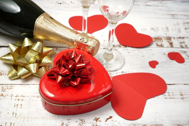 Rote box mit herzform mit schleife, flasche champagner und zwei gläsern