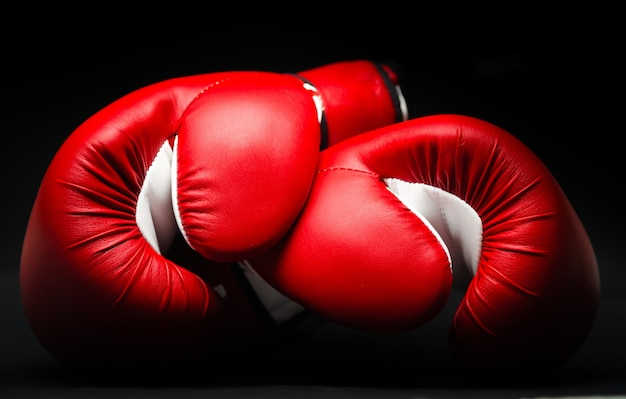 Rote boxhandschuhe auf schwarzem hintergrund