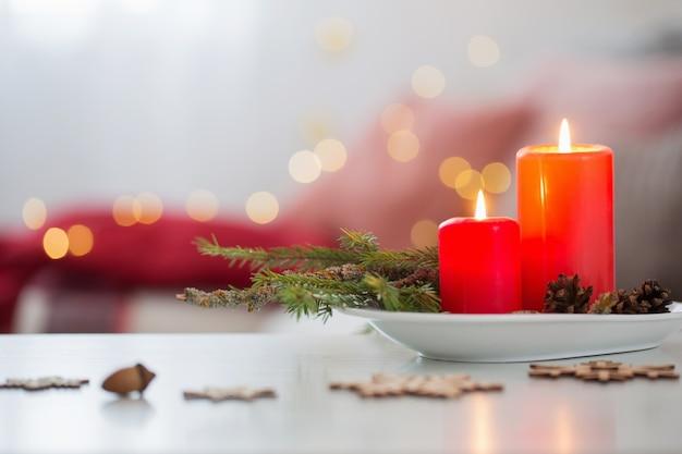 Rote brennende kerzen auf weißem tisch im wohnzimmer