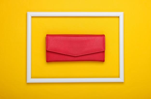 Rote brieftasche in einem weißen rahmen auf gelber oberfläche